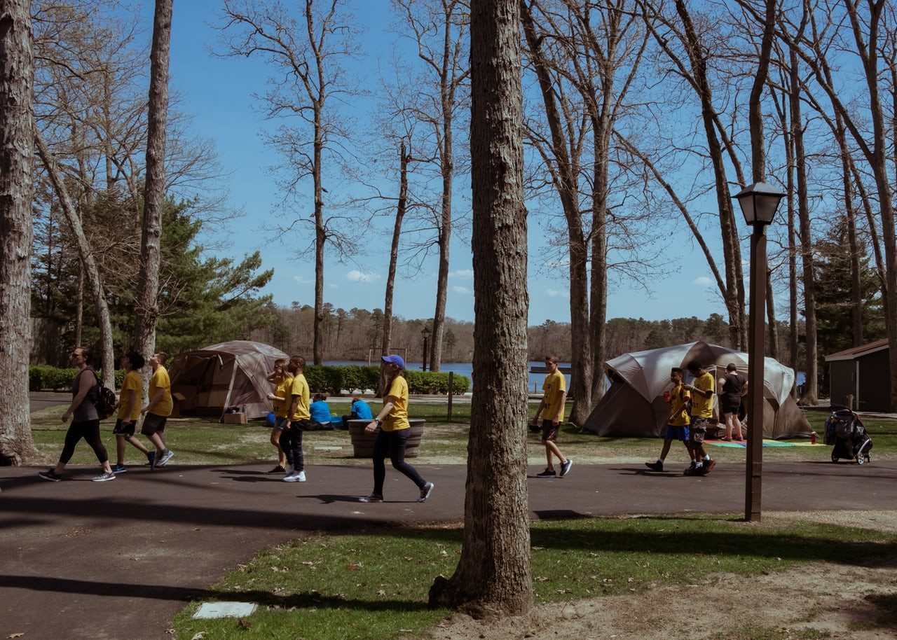 A group of children and accompanying adults walk past the Decompression Tents, located in the Six Flags Fantasy Forest.