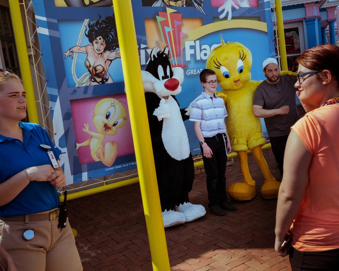 A boy and a young man pose for a photo together with Looney Tunes characters Sylvester the cat and Tweety Bird.